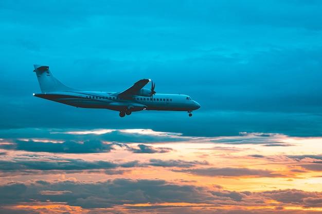 Avion commercial volant au-dessus des nuages dans une lumière spectaculaire au coucher du soleil.