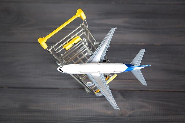 L'avion dans le panier. concept d'achat de billets d'avion sur une surface en bois grise