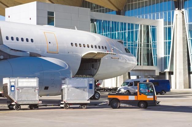 Avion debout dans le parking de l'aéroport, prêt à charger les bagages des passagers.