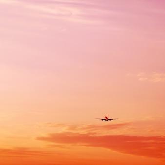 Avion décollant et s'élevant haut dans le concept de vacances de ciel coucher de soleil rose