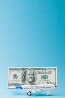 Avion et dollars sur fond bleu. concept de voyage, espace de copie