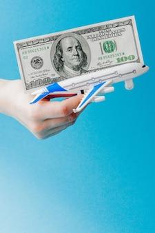 Avion et dollars en main de femme sur bleu