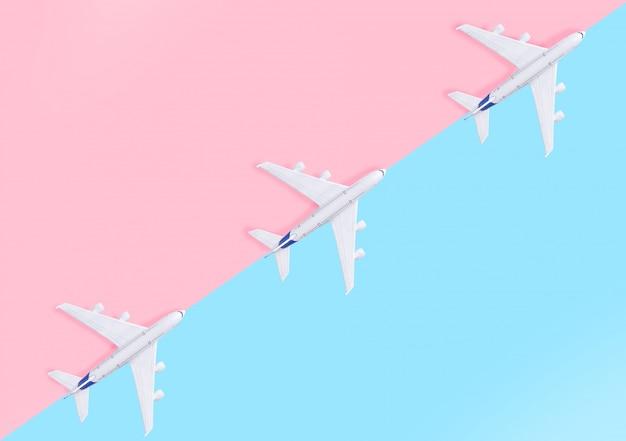 Avion sur fond rose et bleu pastel avec vue de dessus et espace de copie.