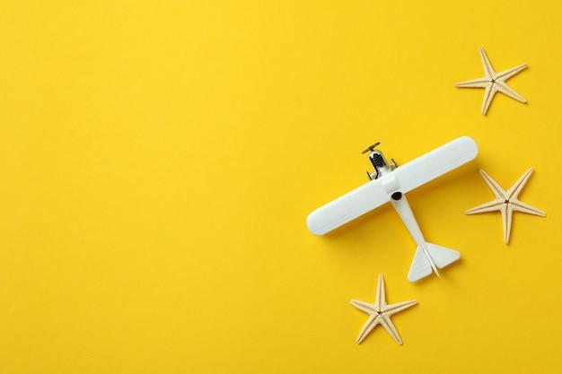 Avion jouet et étoiles de mer sur fond jaune
