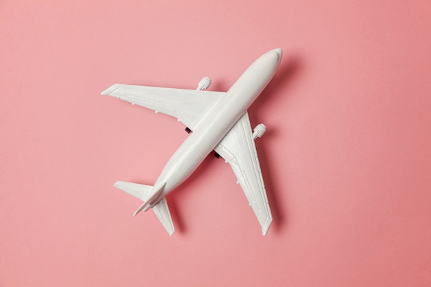 Avion jouet sur fond rose coloré
