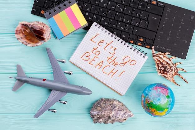 Avion jouet avec globe, coquillages et clavier sur fond bleu. voyage de concept et vacances à la plage.