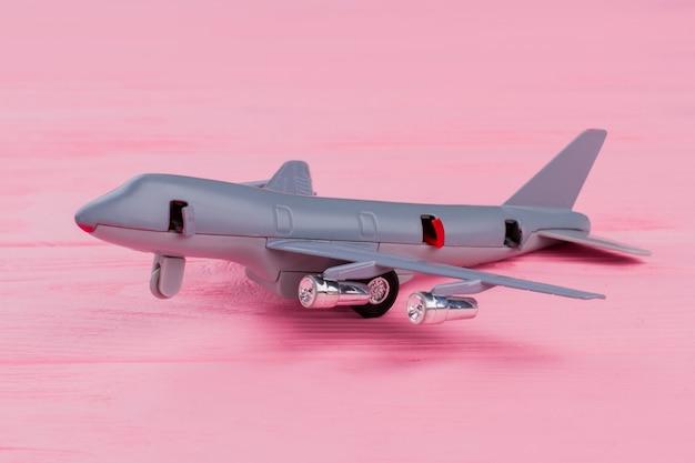 Avion jouet miniature sur fond rose. avion de couleur grise sur un bureau en bois.