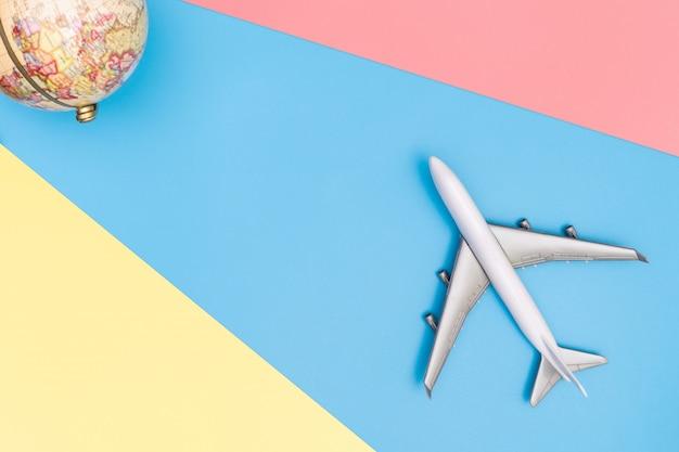 Avion jouet parcourt le concept du monde sur bleu rose jaune