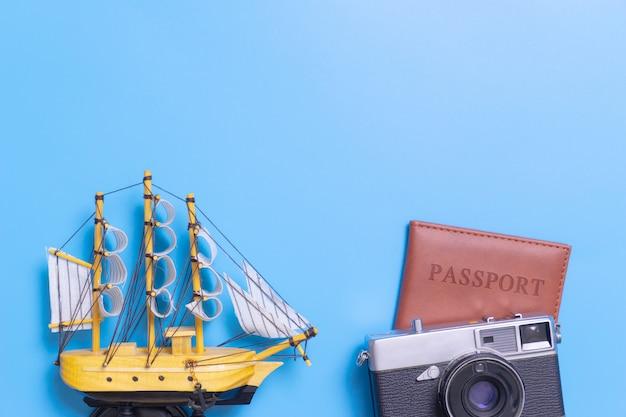 Avion jouet sur le passeport avec appareil photo vintage sur l'espace de copie bleu