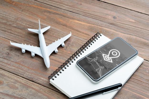 Avion jouet et smartphone sur cahier vierge