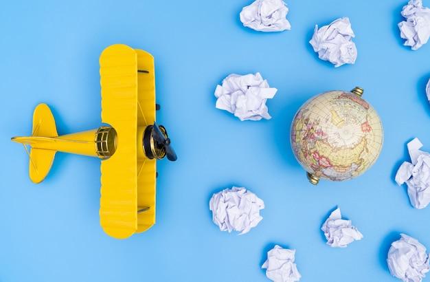 Un avion jouet vole le nuage de papier vers le monde