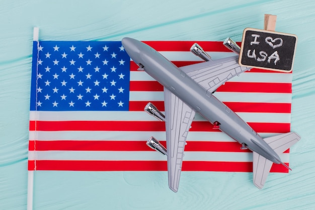 Avion de ligne jouet à plat portant sur le drapeau des états-unis. concept de voyage aux états-unis. concept de vol vers les états-unis.