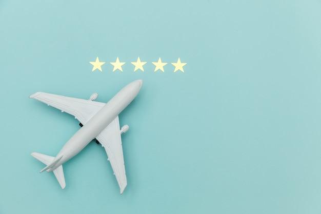 Avion miniature miniature tout simplement plat et 5 étoiles sur fond tendance coloré bleu pastel. voyage en avion vacances été week-end été mer aventure voyage voyage billet tour concept.