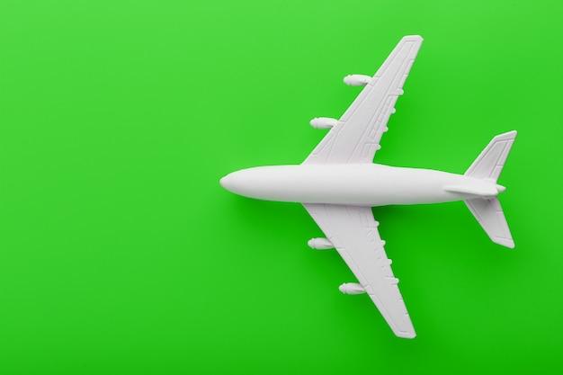 Avion modèle passager blanc sur un fond vert vif