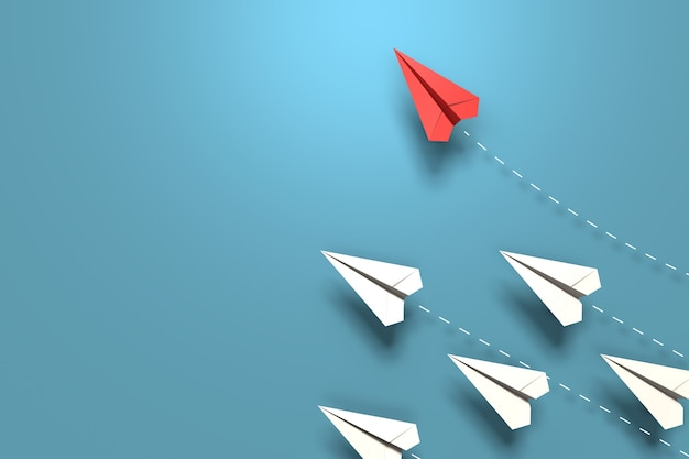 L'avion origami en papier rouge a une direction individuelle à partir d'avions blancs uniques de manière différente