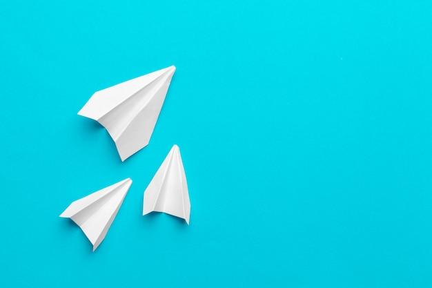 Avion en papier blanc sur un bleu