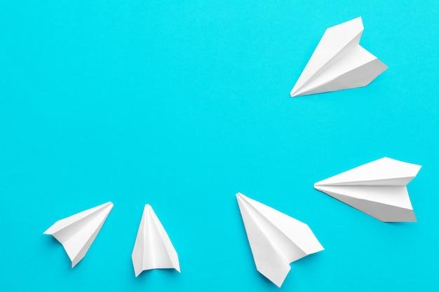 Avion en papier blanc sur bleu