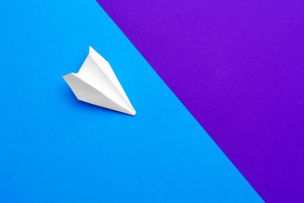 Avion en papier blanc sur un bloc de couleur bleu et violet