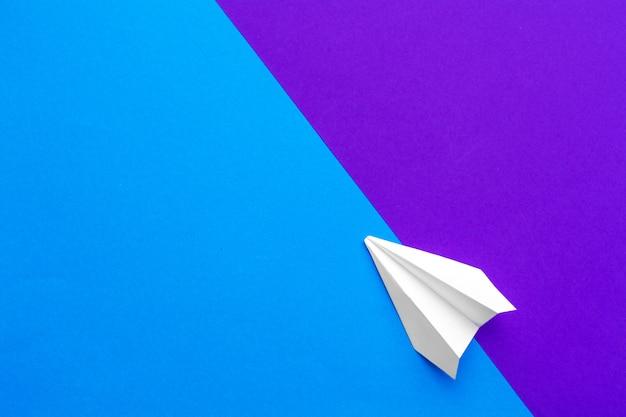 Avion en papier blanc sur un bloc de couleur fond bleu et violet
