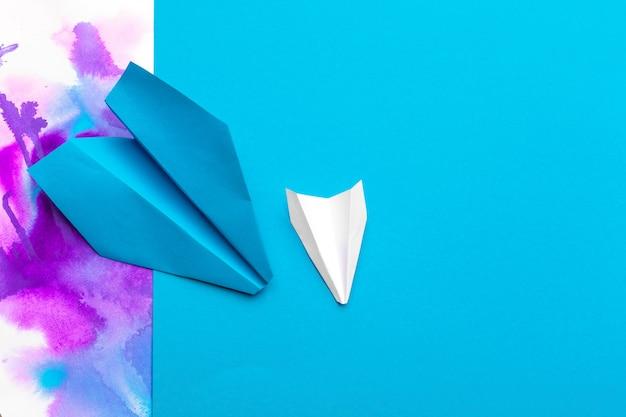 Avion en papier blanc sur un bloc de couleur