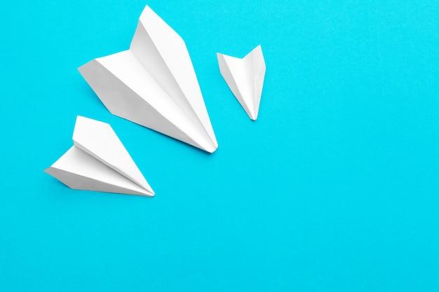 Avion en papier blanc sur fond bleu