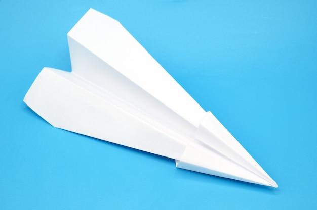Avion en papier blanc sur fond bleu.