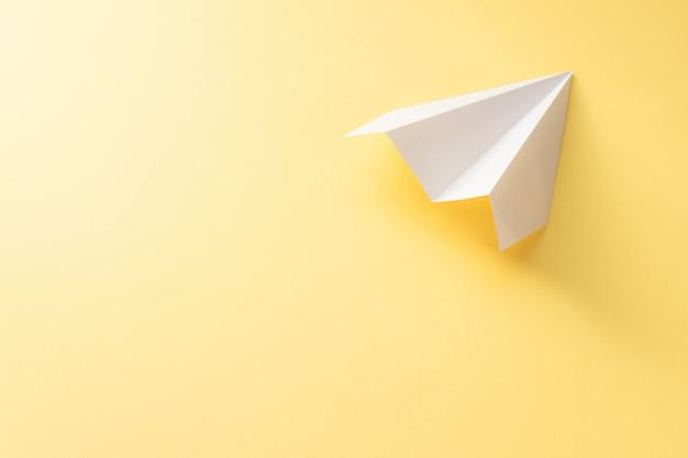 Avion en papier blanc sur fond jaune. concept de voyage coloré