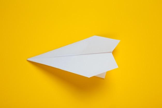 Avion en papier blanc sur fond jaune