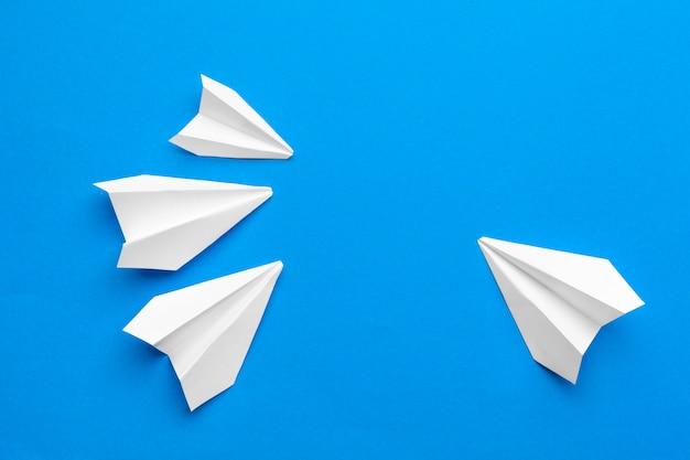 Avion en papier blanc sur un fond de papier marine