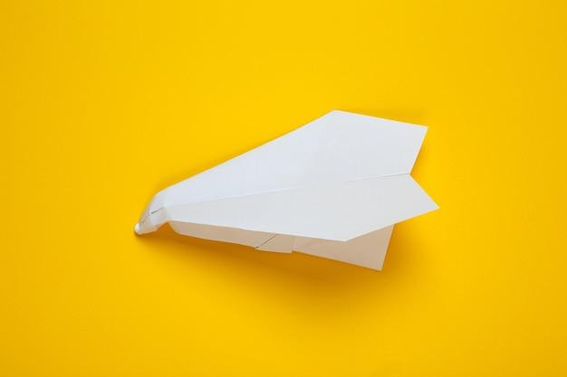 Avion en papier blanc froissé sur fond jaune