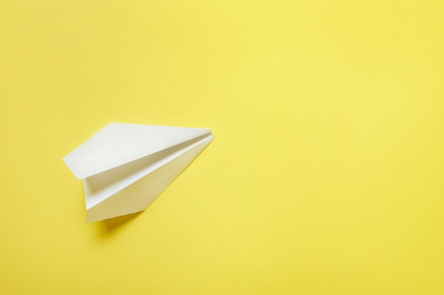 Un avion en papier blanc isolé. mise à plat, vue de dessus