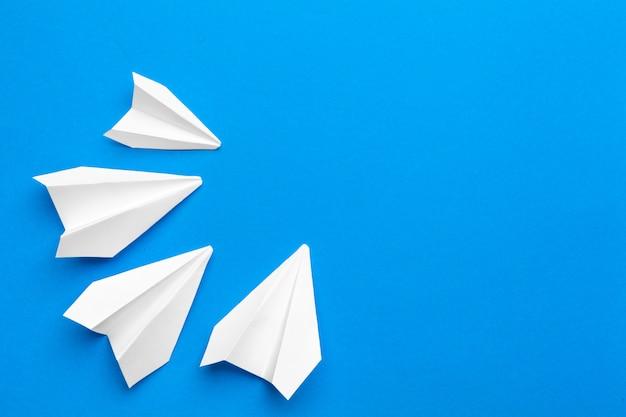 Avion en papier blanc sur un papier bleu marine