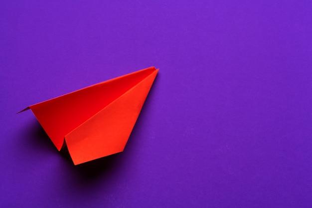 Avion en papier blanc sur un violet