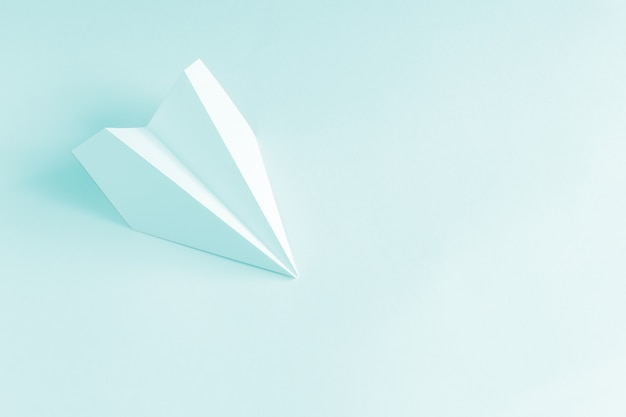 Avion en papier bleu sur fond bleu