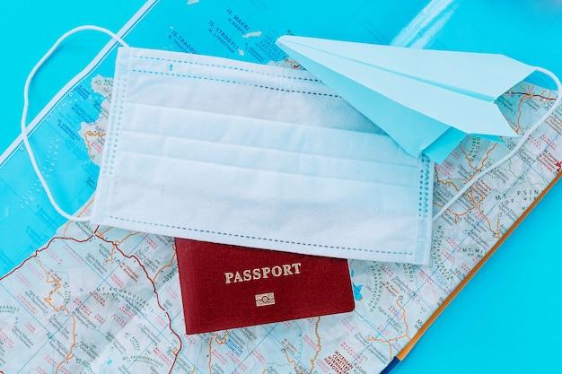 Avion en papier bleu, passeport et masque de protection