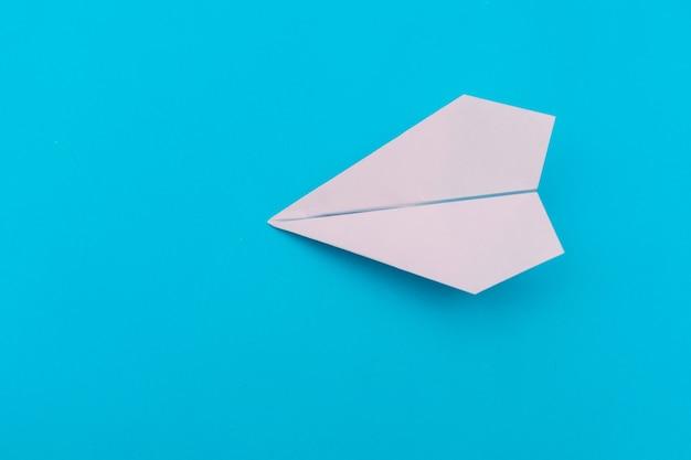 Un avion en papier sur un bleu.