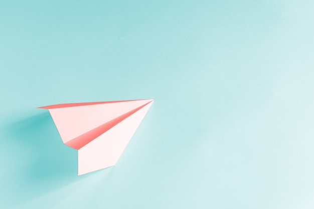 Avion en papier corail sur fond bleu pâle. concept de couleur tendance 2019