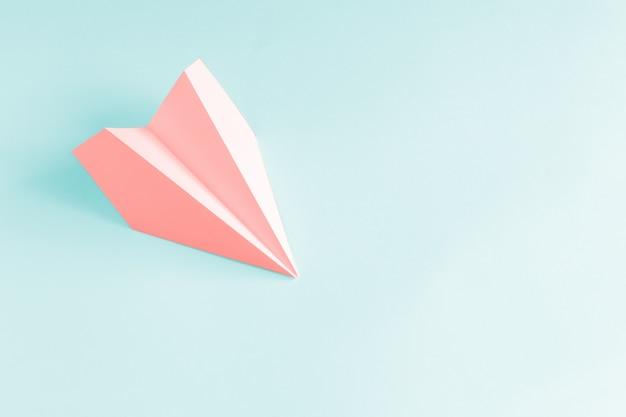 Avion en papier corail sur fond bleu pâle.