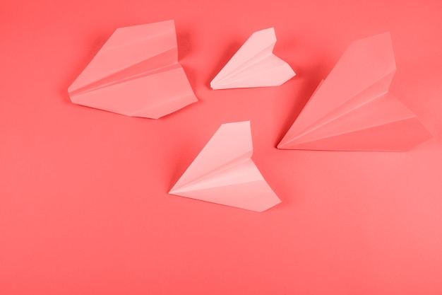 Avion en papier corail et rose sur fond coloré