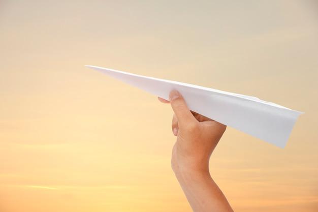 Avion en papier dans la main sur le ciel