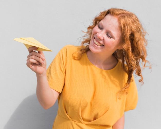 Avion en papier et femme souriante