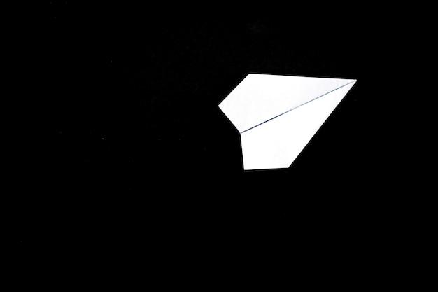 Un avion en papier sur fond noir.