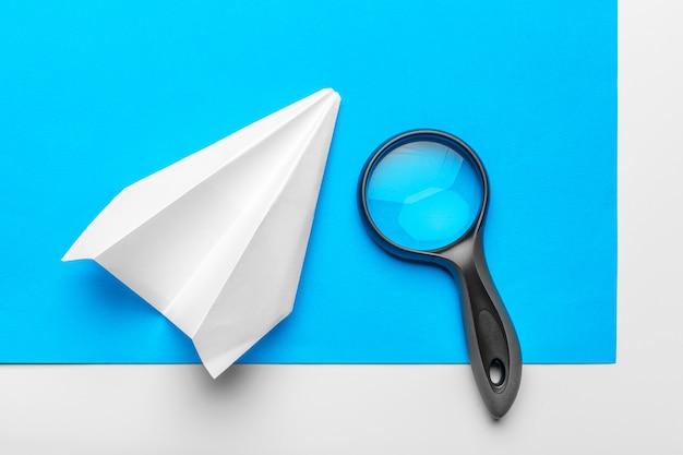 Avion en papier avec des fournitures de bureau sur bleu