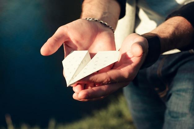 Avion en papier en gros plan de mains mâles.