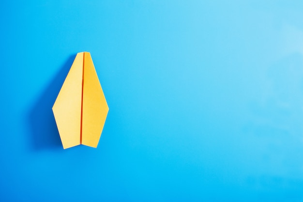 Avion en papier sur le mur de couleur bleue