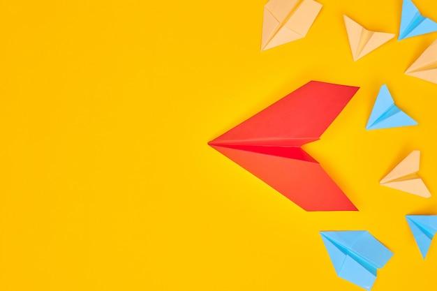 Avion en papier rouge et autres sur fond jaune