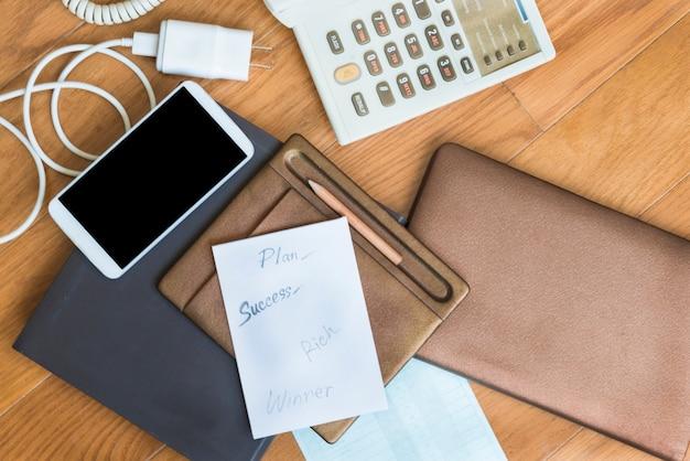 Avion en papier à succès sur tablette marron près de crayon, smartphone, chargeur blanc, téléphone sur tablettes