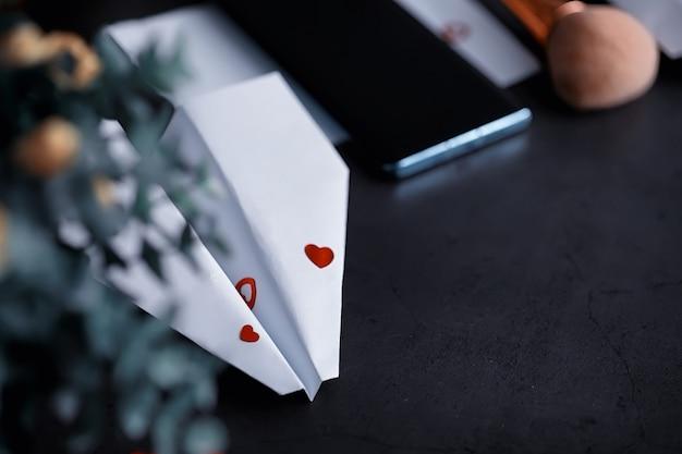 Avion en papier sur la table. modèle en origami sur fond sombre. concept. perte de temps créative.