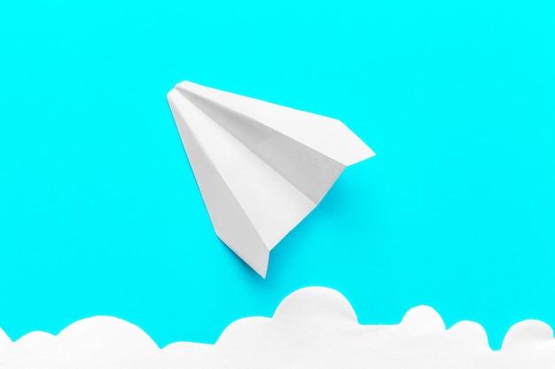 Avion en papier volant dans les nuages sur bleu