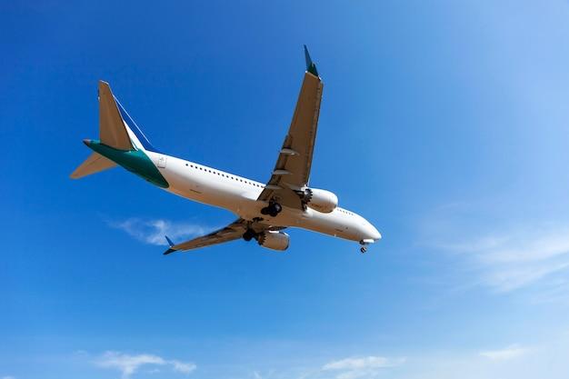 Avion de passagers d'atterrissage clair fond bleu de ciel et nuages